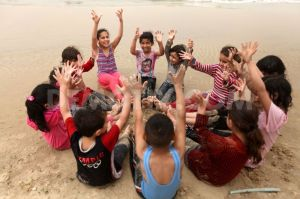 1364847107-palestinian-children-play-on-the-beach-in-gaza-city_1926722